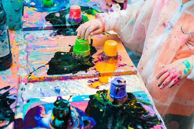 Kleine kinderhände gießen acrylfarbe auf eine leinwand