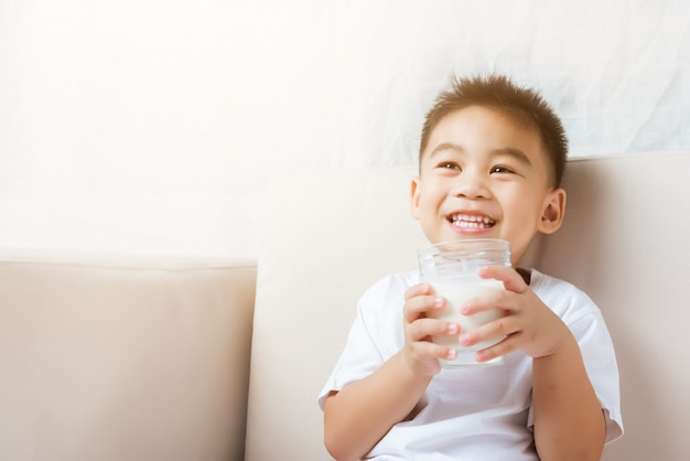 Kleine kinderjungenhand, die milchglas hält, das er weiße milch trinkt