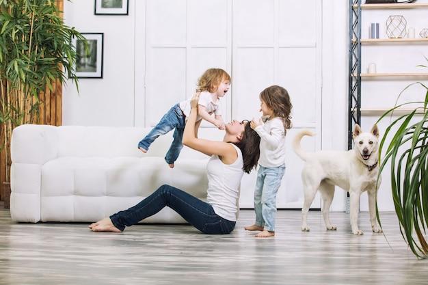 Kleine kindermädchen sind schön und süß mit mutter und hund zu hause zusammen glücklich