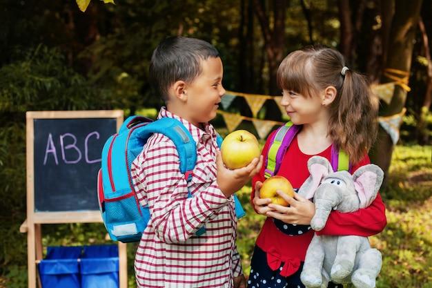 Kleine klassenkameraden mit rucksäcken. zurück zur schule. das konzept der bildung, der schule