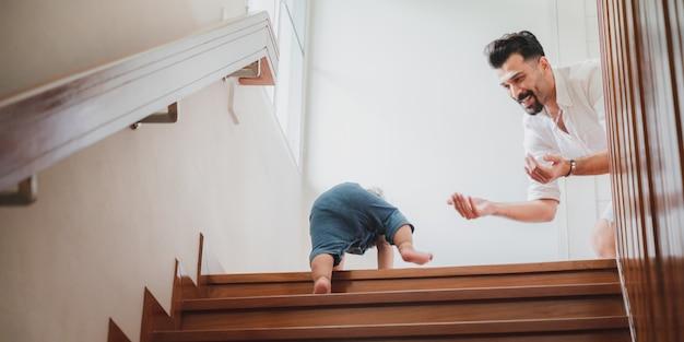 Kleine kleinkinder mit erstem schritt mit treppe zu hause, kleine baby-personen spielen gerne und lernen mit der familie zu krabbeln, süßer säugling, der spaß und kinderbetreuung hat