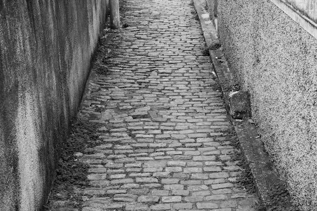 Kleine kopfsteinpflasterstraße mit stein- und seitenwänden, die schwarz-weiße grafiken bilden