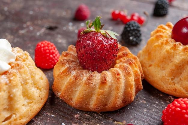 Kleine kuchen mit erdbeeren und sahne auf braunem rustikalem obstbeeren-backkuchen-keks