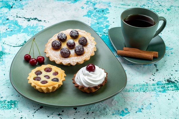 Kleine kuchen mit früchten innerhalb der grünen platte zusammen mit tee und zimt auf blauem, süßem kuchen backen kuchen