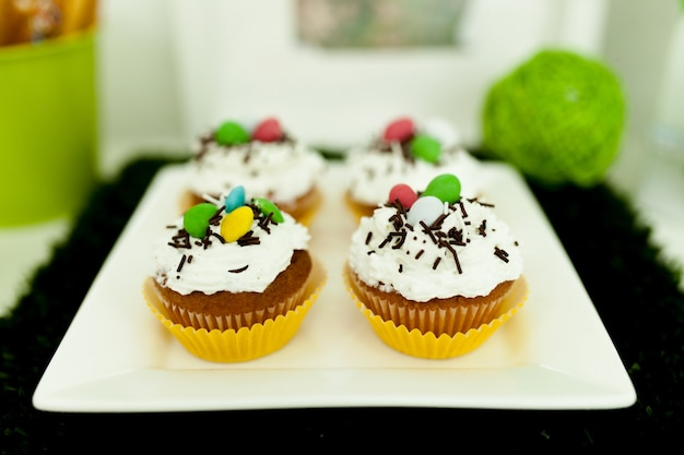 Kleine kuchen mit gefärbt auf einer weißen platte