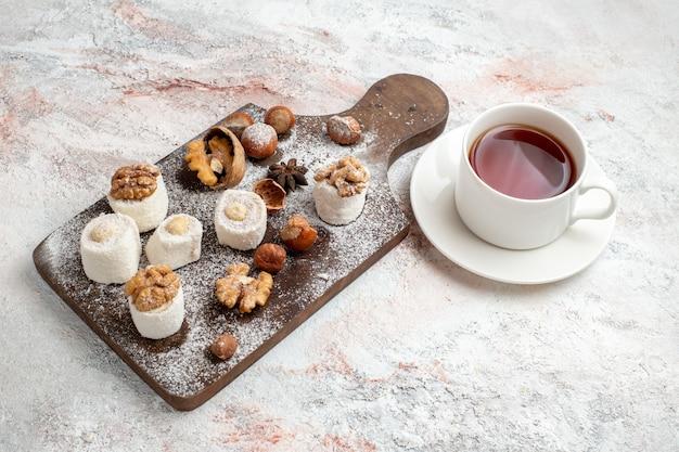Kleine kuchen mit halber draufsicht mit walnusstasse tee und haselnüssen auf dem weißen nusskuchen-kekszuckersüßkeks