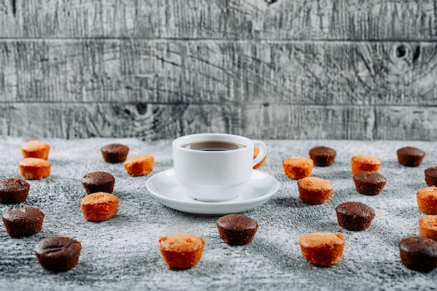 Kleine kuchen mit hohem blickwinkel und tee auf leicht strukturiertem