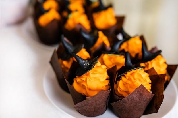 Kleine kuchen mit orange creme und süßen schwarzen hüten auf dem schokoriegel für die feier von halloween