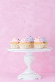 Kleine kuchen mit rosa und violetter creme auf weißem schäbigem shic stand auf pastellrosahintergrund