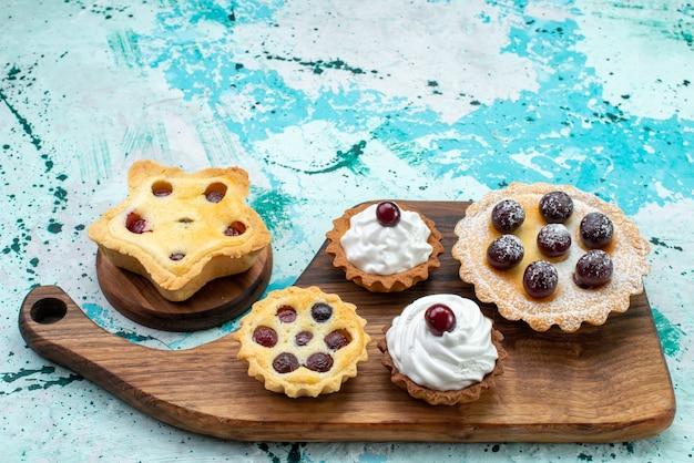 Kleine kuchen mit sahnezuckerpulverfrüchten auf hellblauem kuchencreme-keks-süßem zuckerauflauf