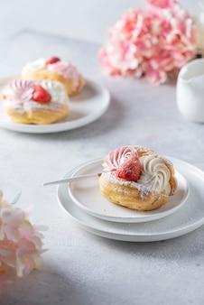 Kleine kuchen mit schlagsahne und erdbeere