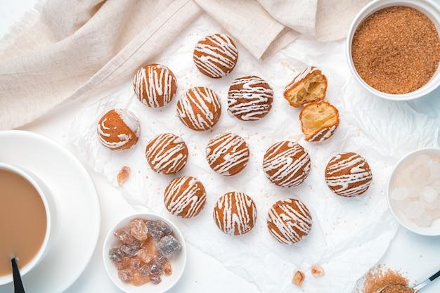 Kleine kuchen mit weißer schokolade auf hellem hintergrund mit kaffee und zucker. draufsicht, horizontal.