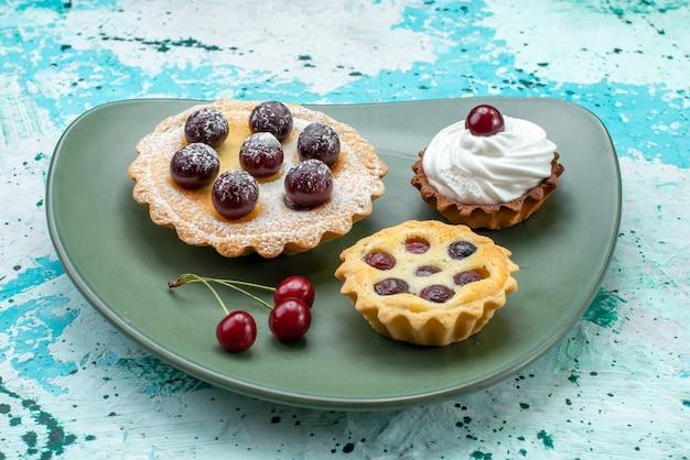Kleine kuchen mit zuckerpulver fruchtcreme in platte auf hellblau, kuchencreme frucht süß