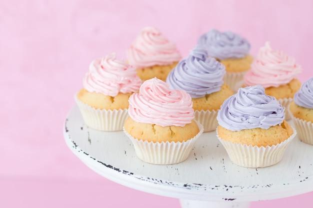Kleine kuchen verziert mit rosa und violetter buttercreme auf schäbigem shic stand