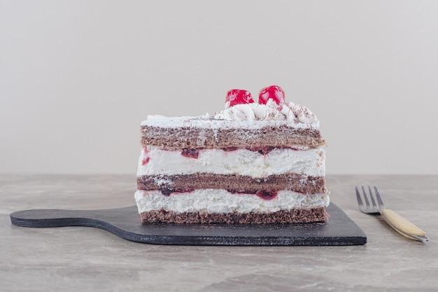 Kleine kuchenscheibe mit sahne, kirsche und kakaopulver auf einem brett auf marmor
