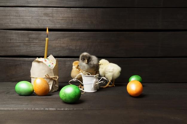 Kleine küken osterkuchen und bunte eier auf einem dunklen holztisch