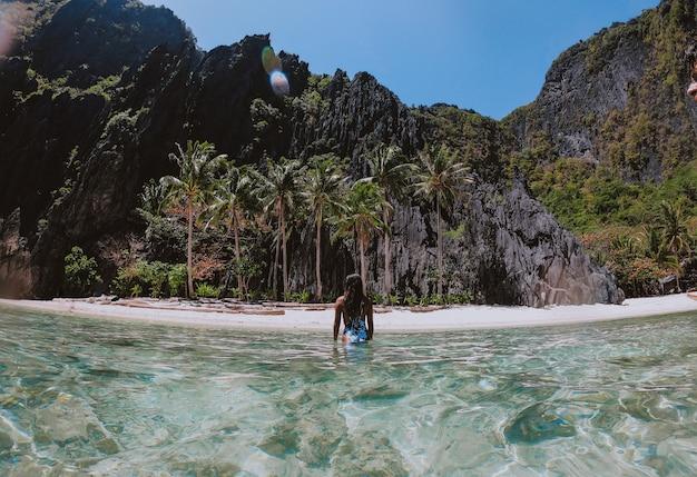 Kleine lagune in el nido. frau, die zeit im durchsichtigen kristallwasser mit tropischem dschungel genießt. konzept über reisen und natur