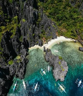 Kleine lagune in el nido. menschen, die auf dem weißen sand mit tropischem dschungel gehen. konzept über reisen und natur