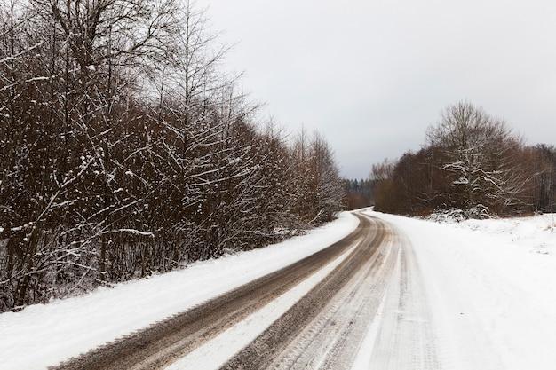 Kleine landstraße mit schneestraße bedeckt, entlang der waldbäume wachsen