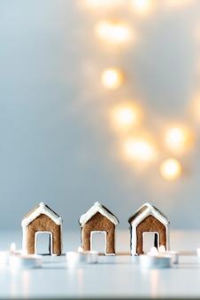 Kleine lebkuchenhäuser, kerzen und weihnachtslichter