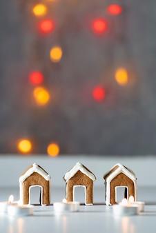 Kleine lebkuchenhäuser und kerzen auf bokehhintergrund. vertikaler rahmen.