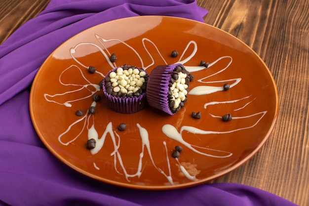 Kleine leckere brownies mit schokoladenstückchen in brauner platte auf holz