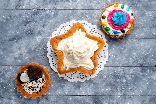 Kleine leckere kuchen der draufsicht mit sahne und verschiedenen bunten bonbons auf dem süßen farbkuchenfoto des hellen tischbonbons