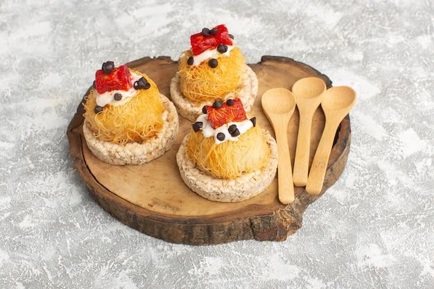Kleine leckere kuchen mit früchten auf braunem holzschreibtisch