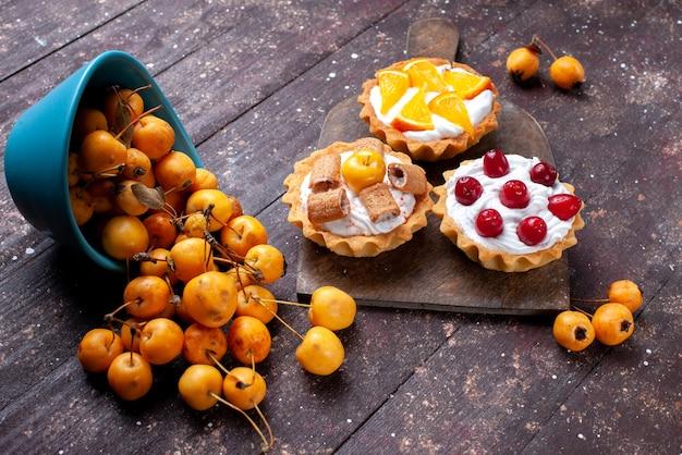 Kleine leckere kuchen mit in sahne geschnittenen früchten und frischen gelben kirschen auf braunem holz, frischem obstkuchen keks süßkirsche