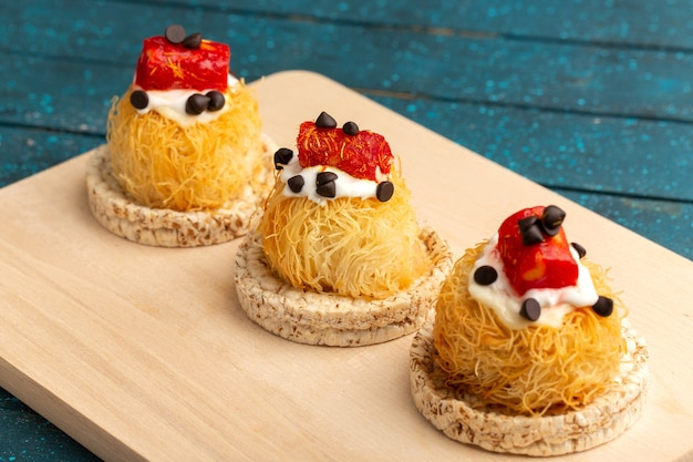Kleine leckere kuchen mit sahne auf holzschreibtisch