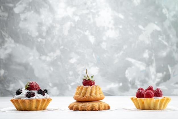 Kleine leckere kuchen mit sahne und beeren auf leichtem, kuchen keks beerenfrucht süßer zucker