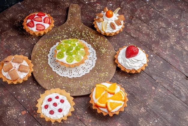 Kleine leckere kuchen mit sahne und verschiedenen geschnittenen früchten auf holzbraun, obstkuchen keks süß backen