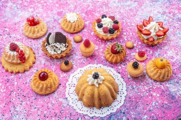 Kleine leckere kuchen mit sahne zusammen mit verschiedenen beeren auf hellem, süßem kuchen-keks-beeren-backtee