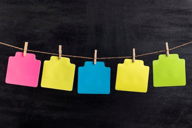 Kleine leere mehrfarbige papierkarten hängen mit wäscheklammer am seil. platz kopieren. platz für ihren text.
