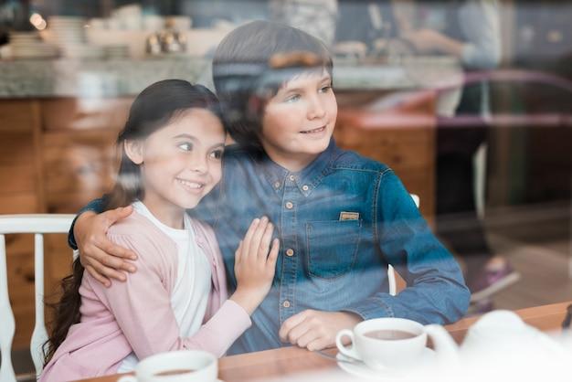 Kleine liebhaber haben ein date im café. kinder umarmen sich.