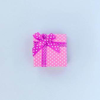 Kleine lila geschenkbox mit band liegt auf veilchen