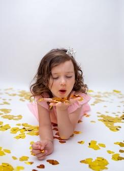 Kleine lockige prinzessin mit einem kranz mit krone liegt mit konfetti aus ihren händen auf einem weißen hintergrund mit einem platz für text