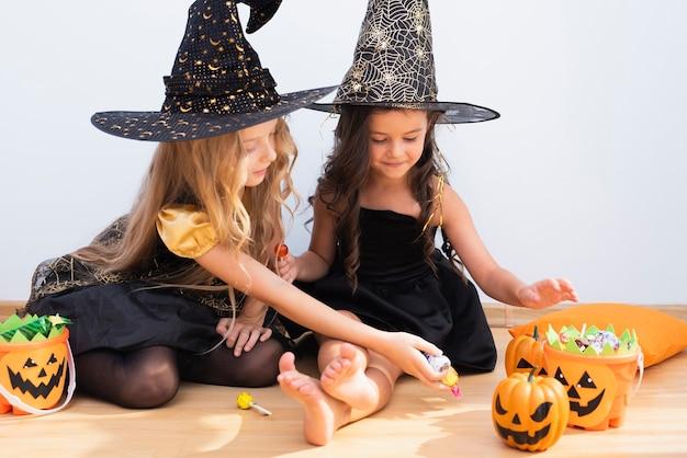 Kleine mädchen der vorderansicht, die auf boden an halloween sitzen