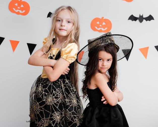 Kleine mädchen der vorderansicht im hexenkostüm für halloween