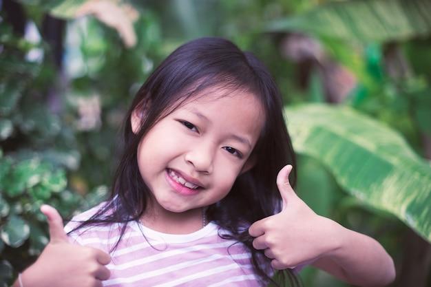 Kleine mädchen des asiatischen lächelns des porträts mit sehr gutem zeichen.