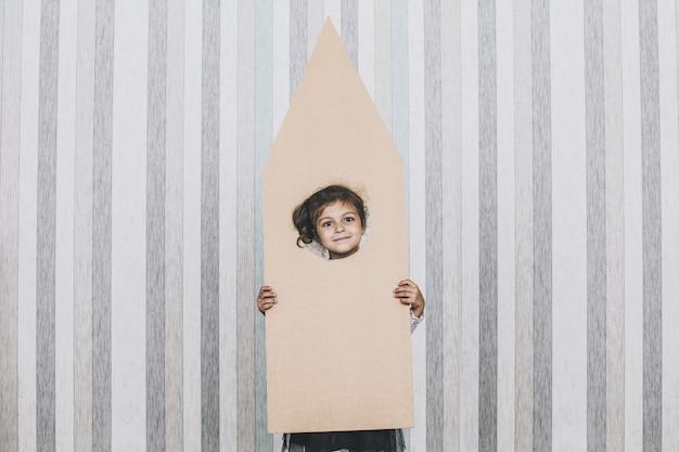 Kleine mädchen des kindes, die raumfahrer mit einer papprakete spielen