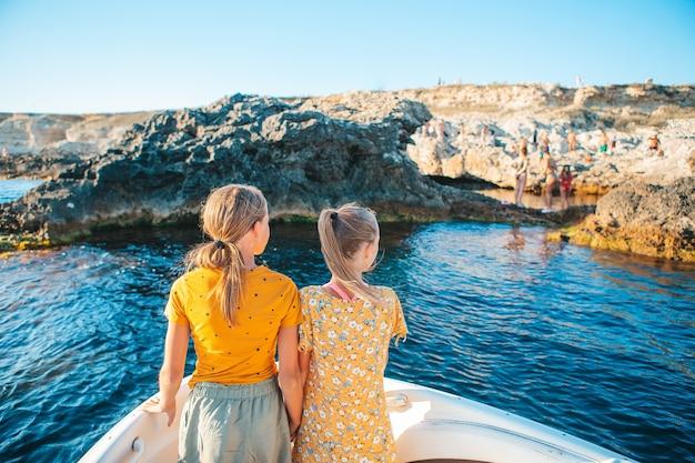 Kleine mädchen, die auf boot im klaren offenen meer segeln