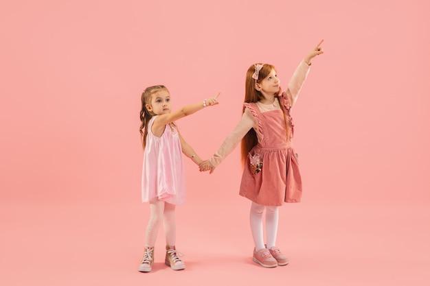 Kleine mädchen, die auf rosa wand zeigen