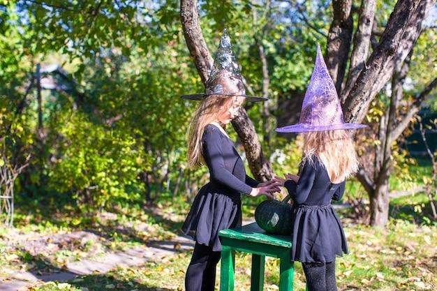 Kleine mädchen, die einen bann auf halloween im hexenkostüm werfen