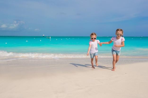 Kleine mädchen, die entlang den weißen strand laufen und spaß haben