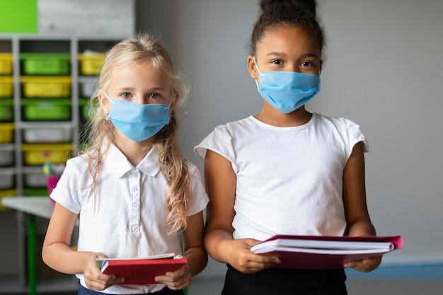 Kleine mädchen, die im unterricht medizinische masken tragen