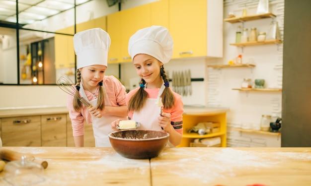 Kleine mädchen, die in kappen kochen, geben butter in die schüssel