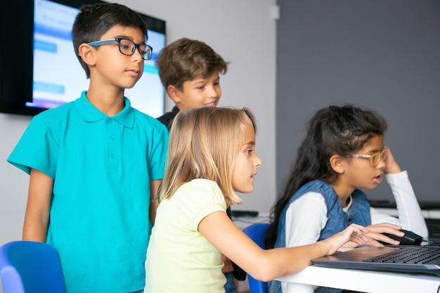 Kleine mädchen, die laptops benutzen, an der computerschule lernen und am tisch sitzen