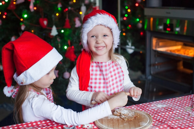 Kleine mädchen, die lebkuchenplätzchen für weihnachten in sankt-hut backen
