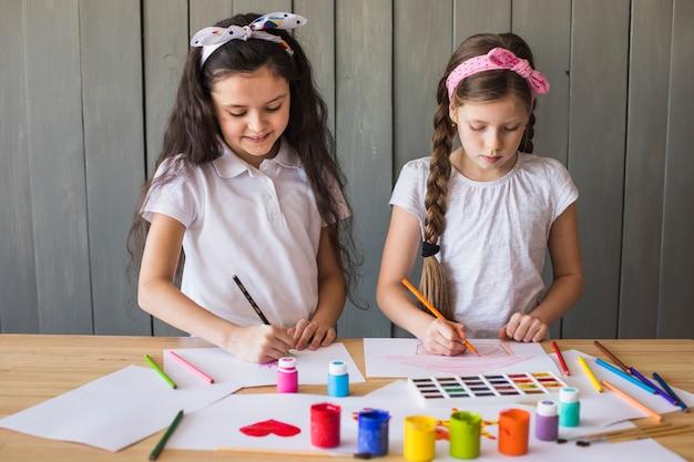 Kleine mädchen, die mit farbigen bleistiften auf weißbuch über dem hölzernen schreibtisch zeichnen